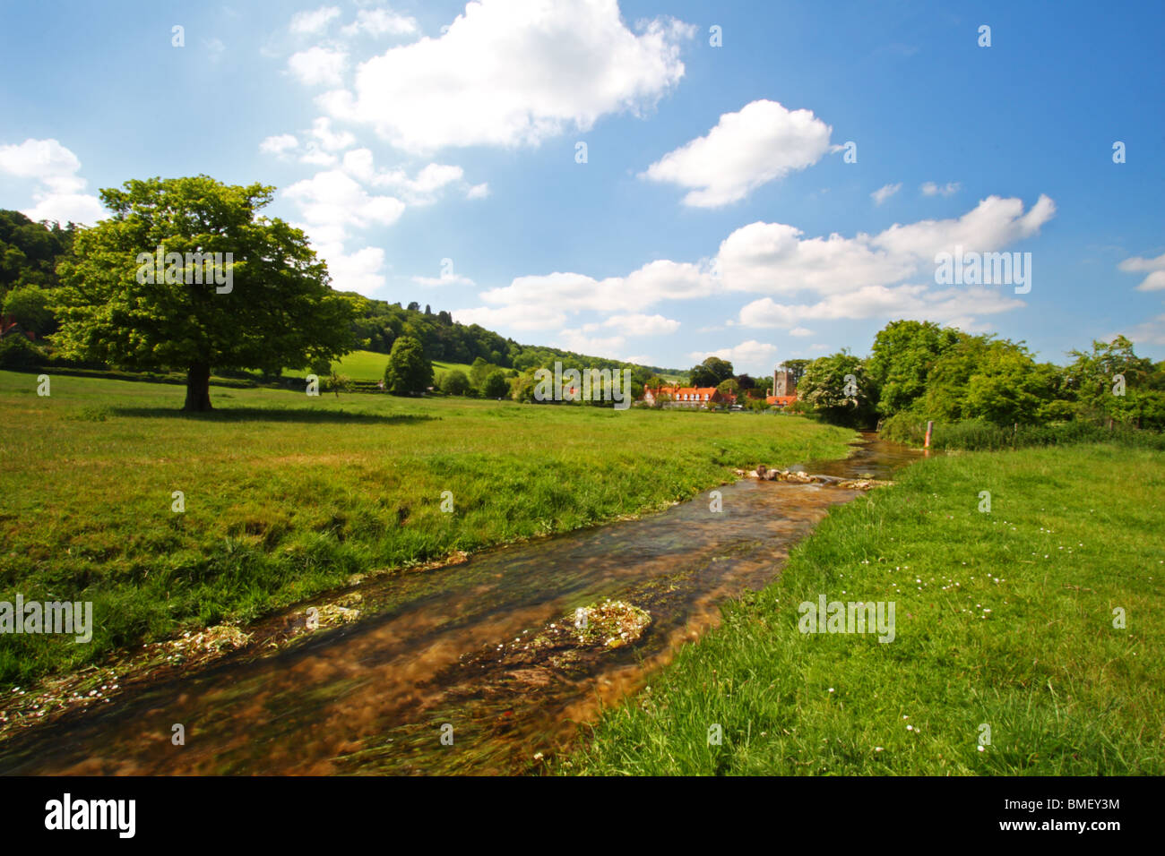 Hambleden Brook with Hambleden village in the background. Buckinghamshire, United Kingdom - Stock Image