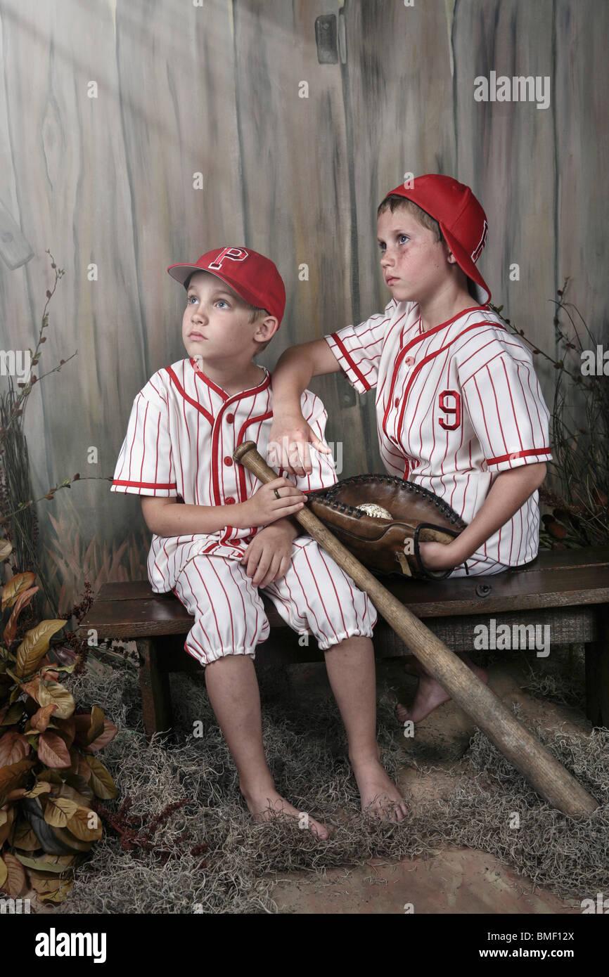 Two Boys Wearing Baseball Uniforms Sitting On A Bench ...