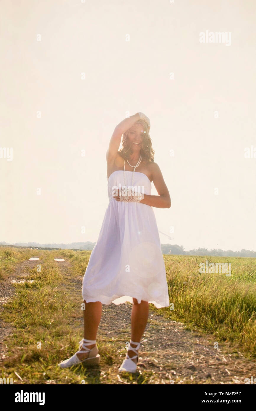 A Bride Standing In The Sun In A Field - Stock Image