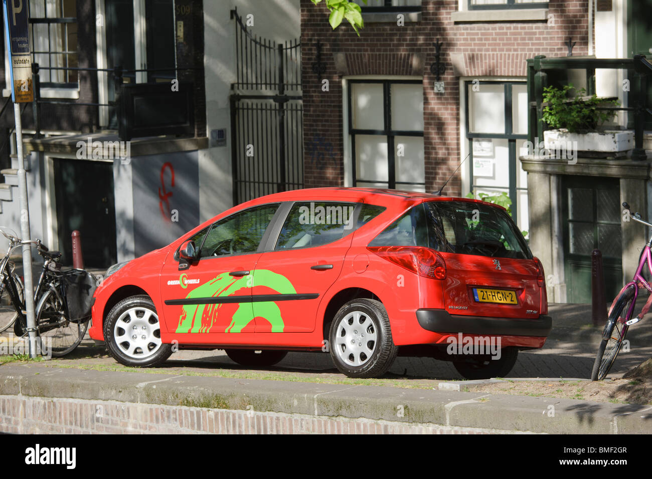 A Green Wheels car for car sharing, dating, short term rental, on a canal in Amsterdam. Peugeot 207. - Stock Image