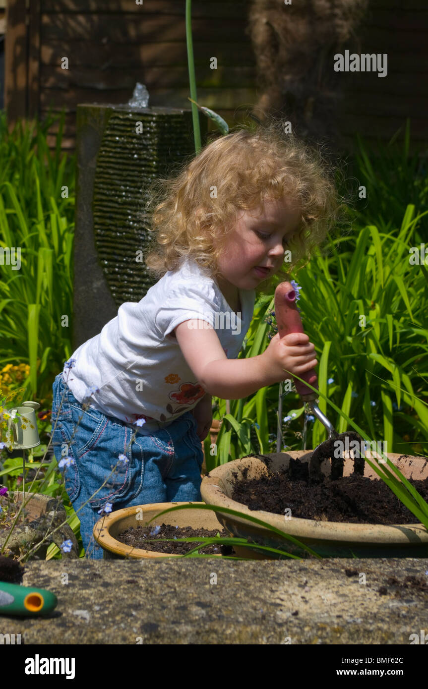 Young Child Digging With A Garden Fork In A Large Flower Pot In The Garden - Stock Image