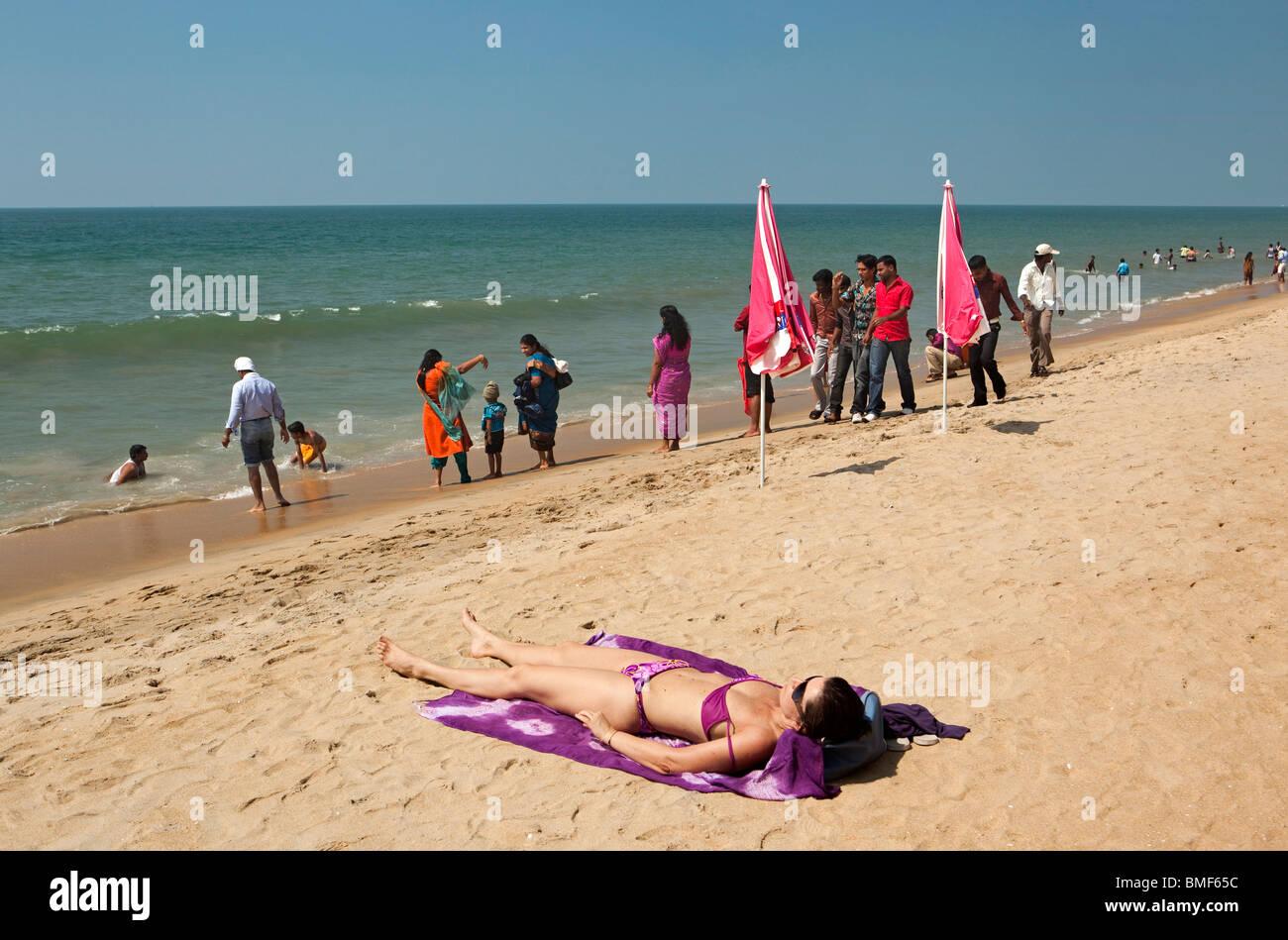 India, Kerala, Vypeen Island, Cherai Beach western sunbather amongst fully dressed Indian visitors - Stock Image