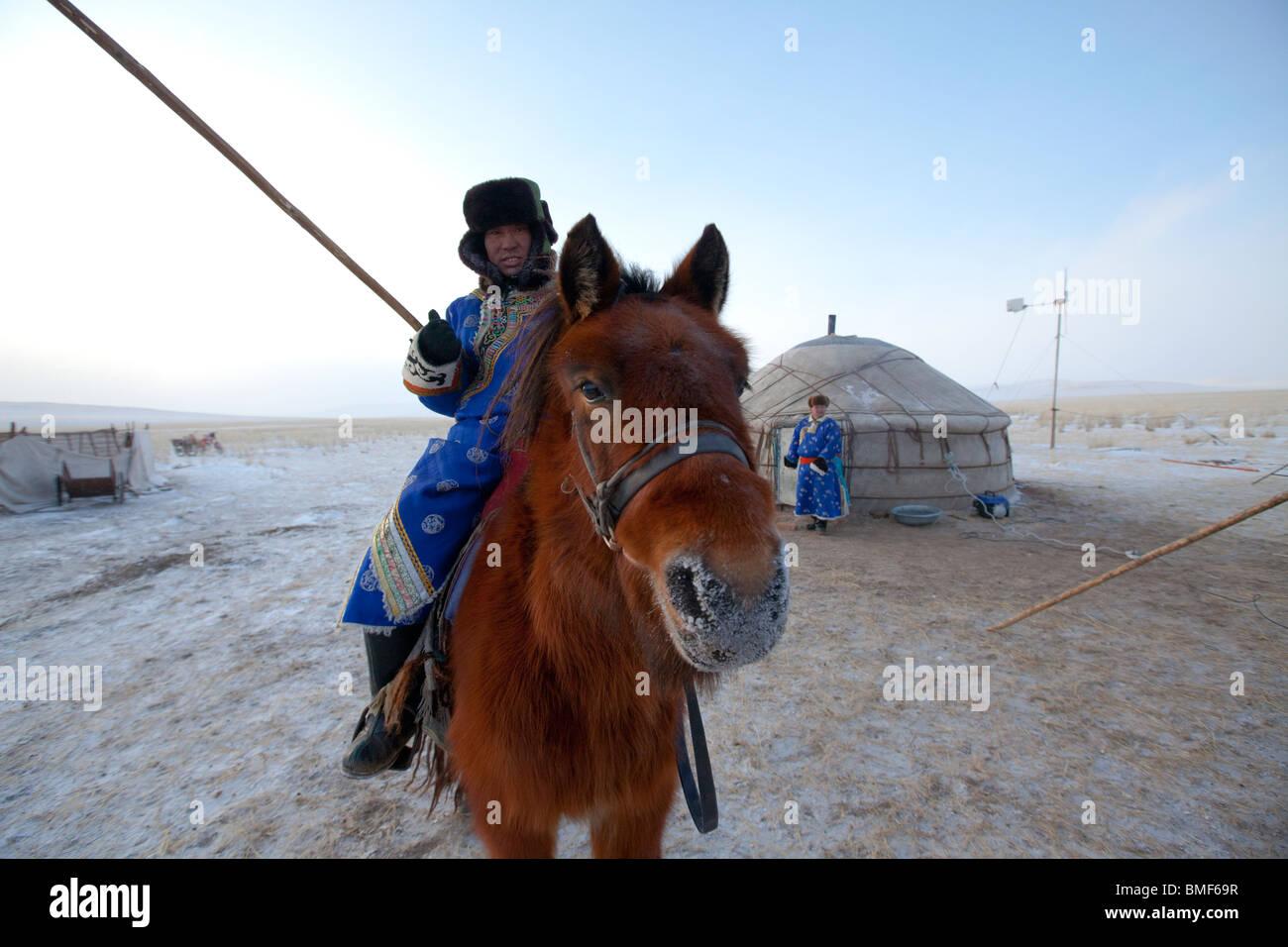 Mongolian men riding horse with horsewhip, Ujimqin Grassland, East Ujimqin Banner, Xilin Gol League, Inner Mongolia, - Stock Image
