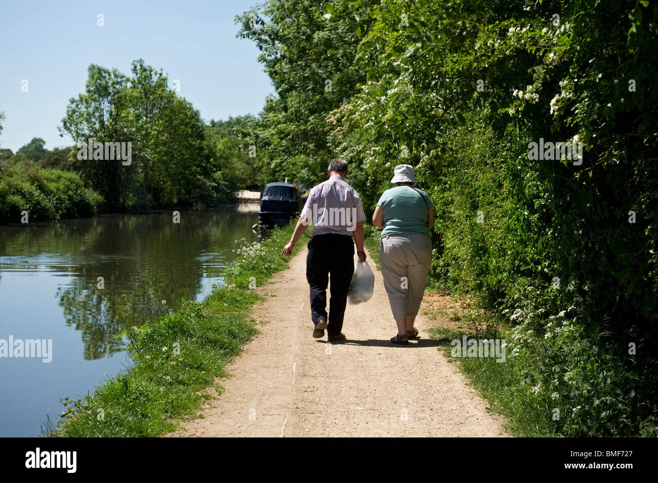 A middle aged couple 50's strolling along a towpath by the Grand Union canal on a sunny day. - Stock Image