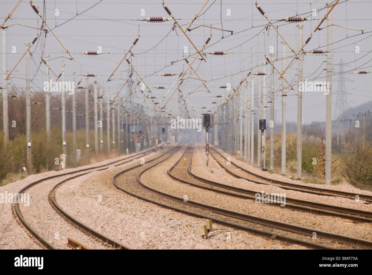 Empty railway tracks and overhead line catenary equipment on a length  of four track railway. Stock Photo