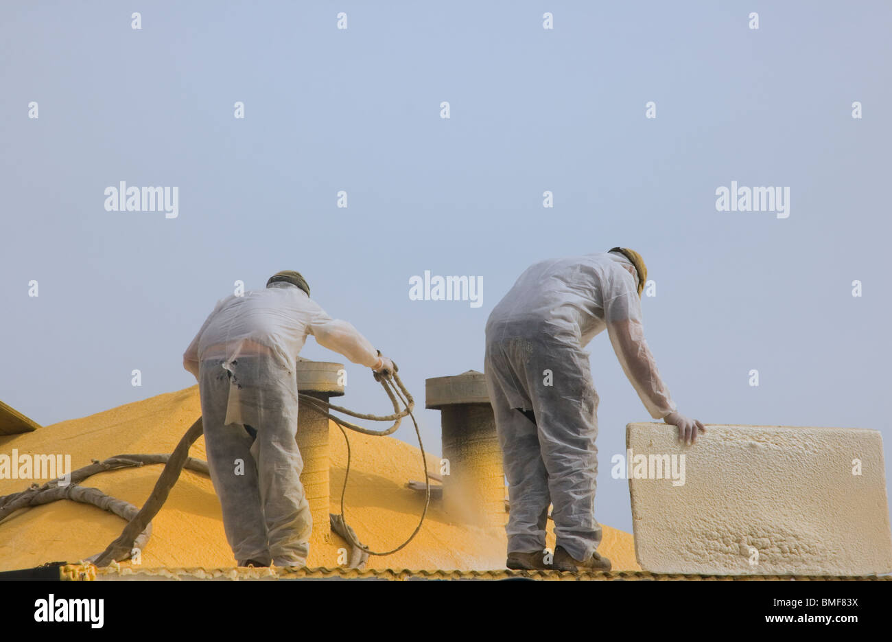 Workmen spray painting the roof of a building with yellow paint. - Stock Image