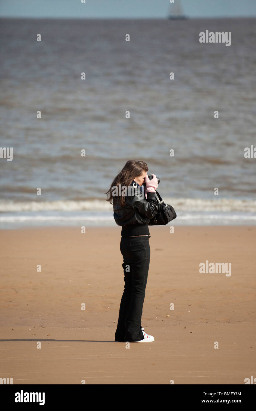 young woman taking a photo on a beach in UK - Stock Image