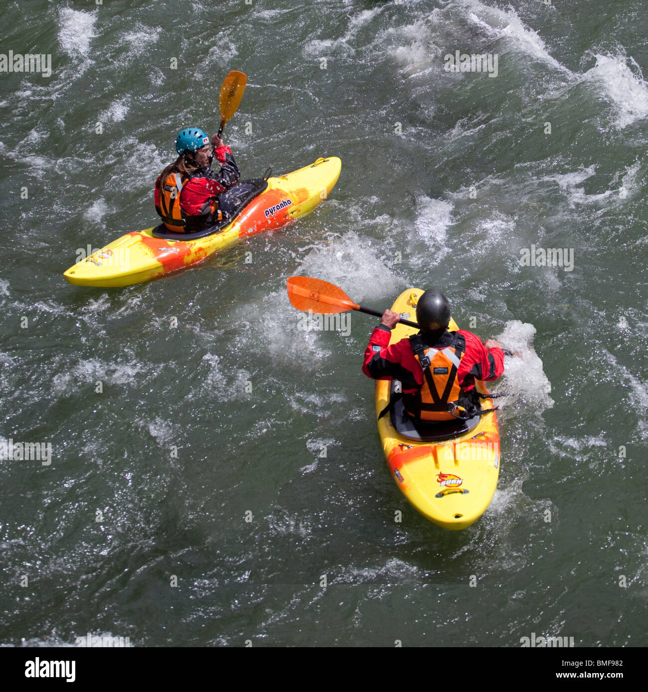 A couple of young men canoeing in river rapids Stock Photo