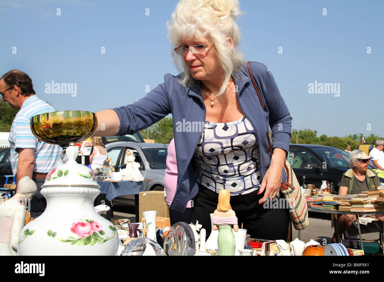 Woman making a purchase at a car boot sale. - Stock Image