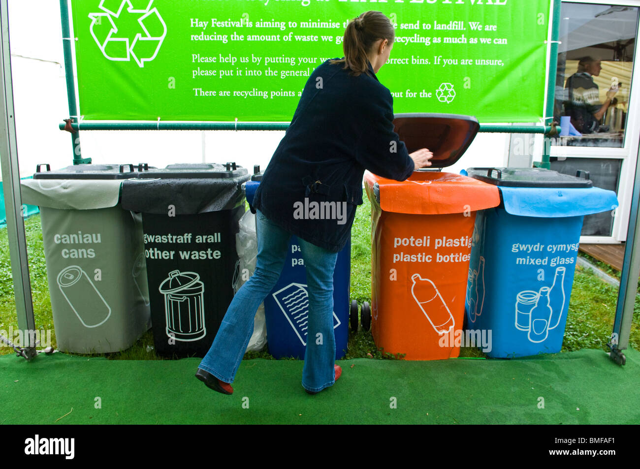 Female placing waste into coloured plastic wheelie bins used for various recyclable waste - Stock Image