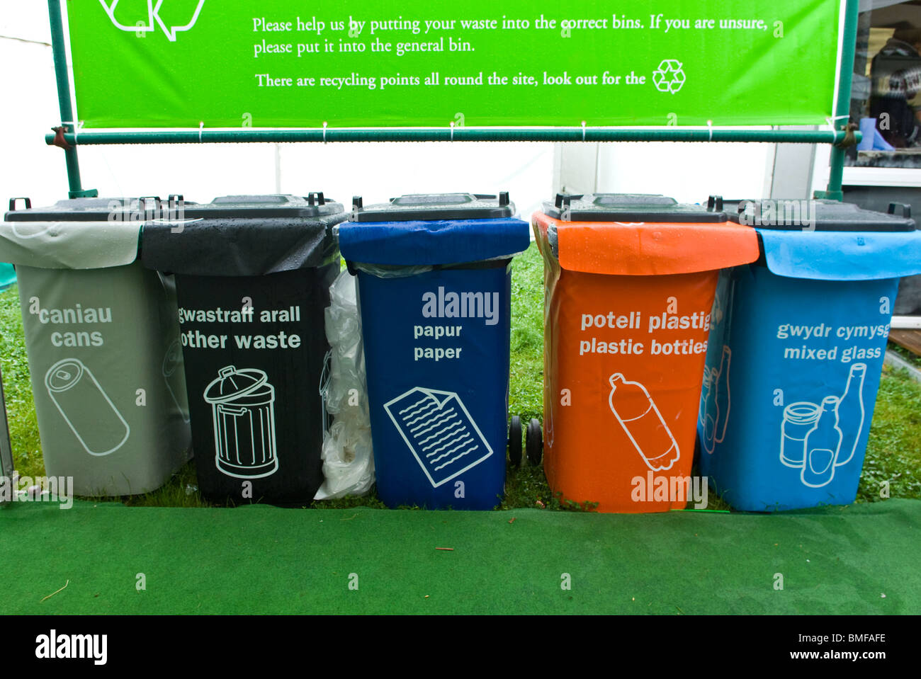 Row of coloured plastic wheelie bins for various recyclable waste - Stock Image