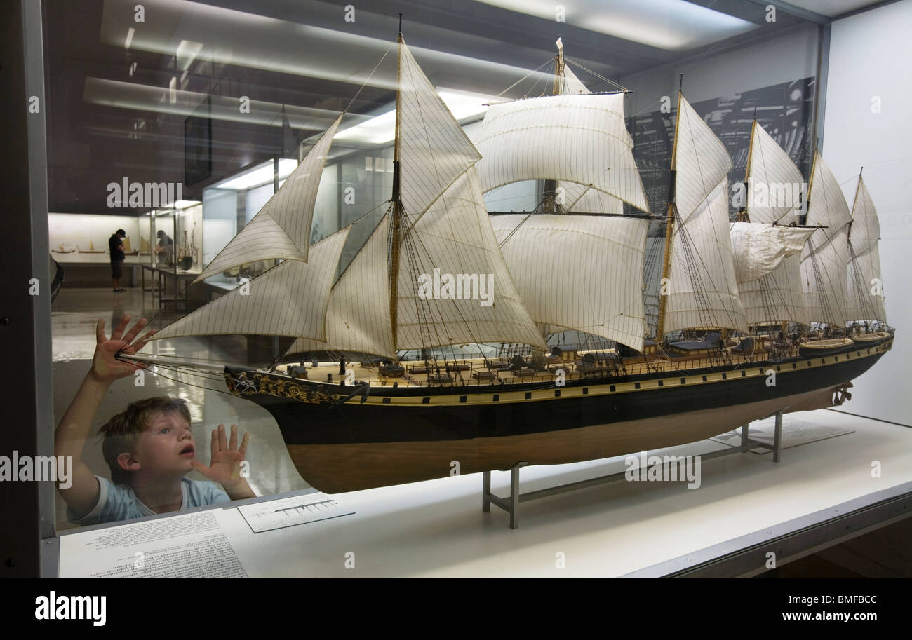 A boy admiring in awe at a XIX century clipper sailboat Stock Photo