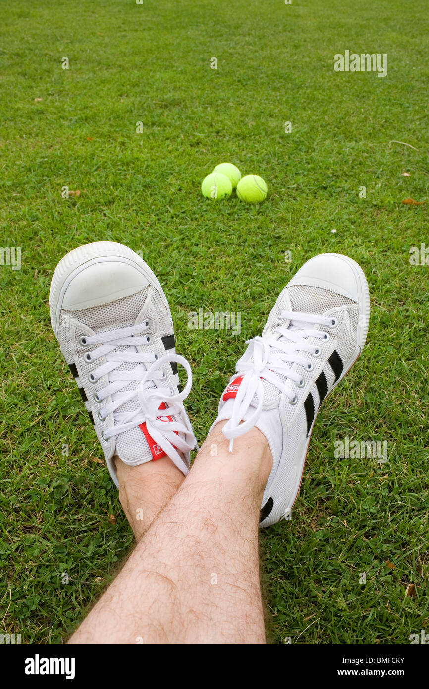 huge selection of b5f78 8ed97 A mans feet wearing a white pair of Adidas trainers and 3 tennis balls. -