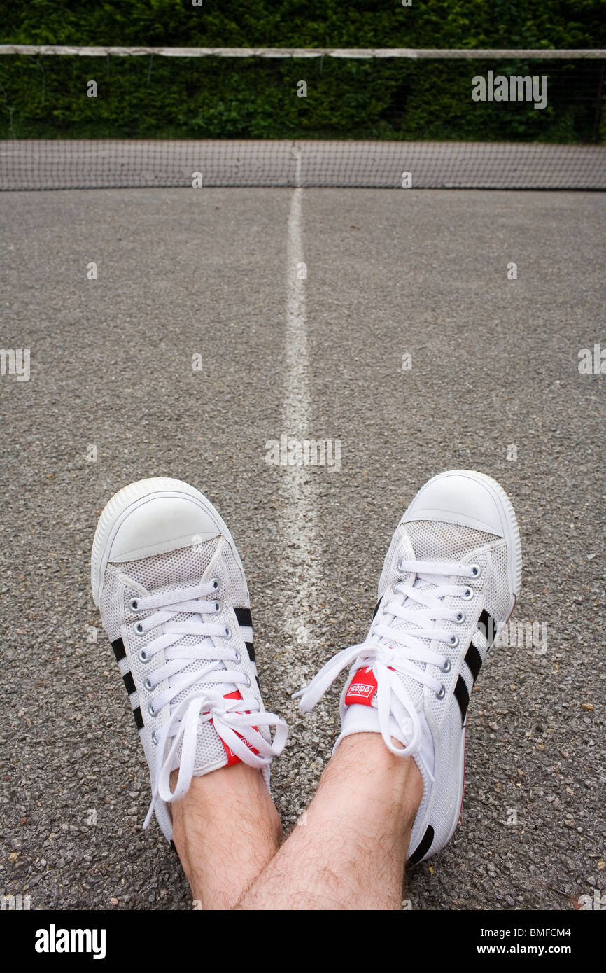 wholesale dealer e33db 23677 A mans feet wearing white Adidas trainers on a tennis court - Stock Image