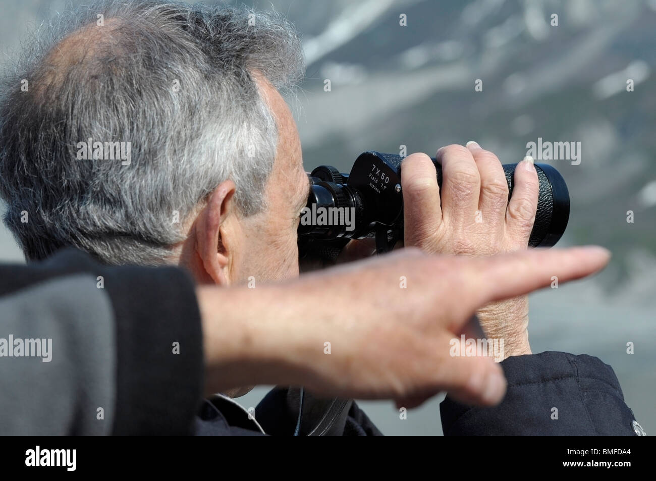 Man Looking through Binoculars and a hand pointing. - Stock Image