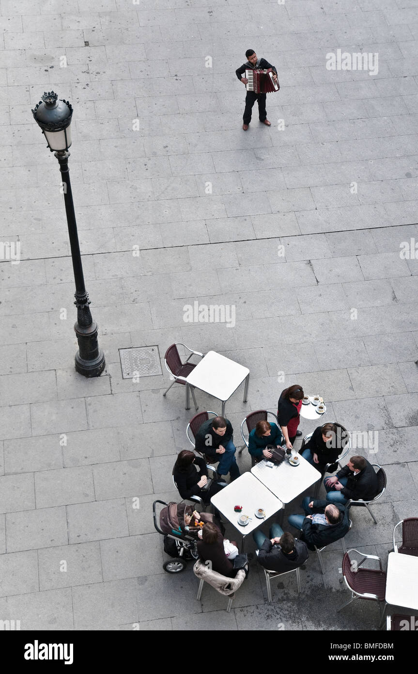 A street musician entertains cafe customers in the Plaza de Santa Cruz in the centre of Madrid. - Stock Image
