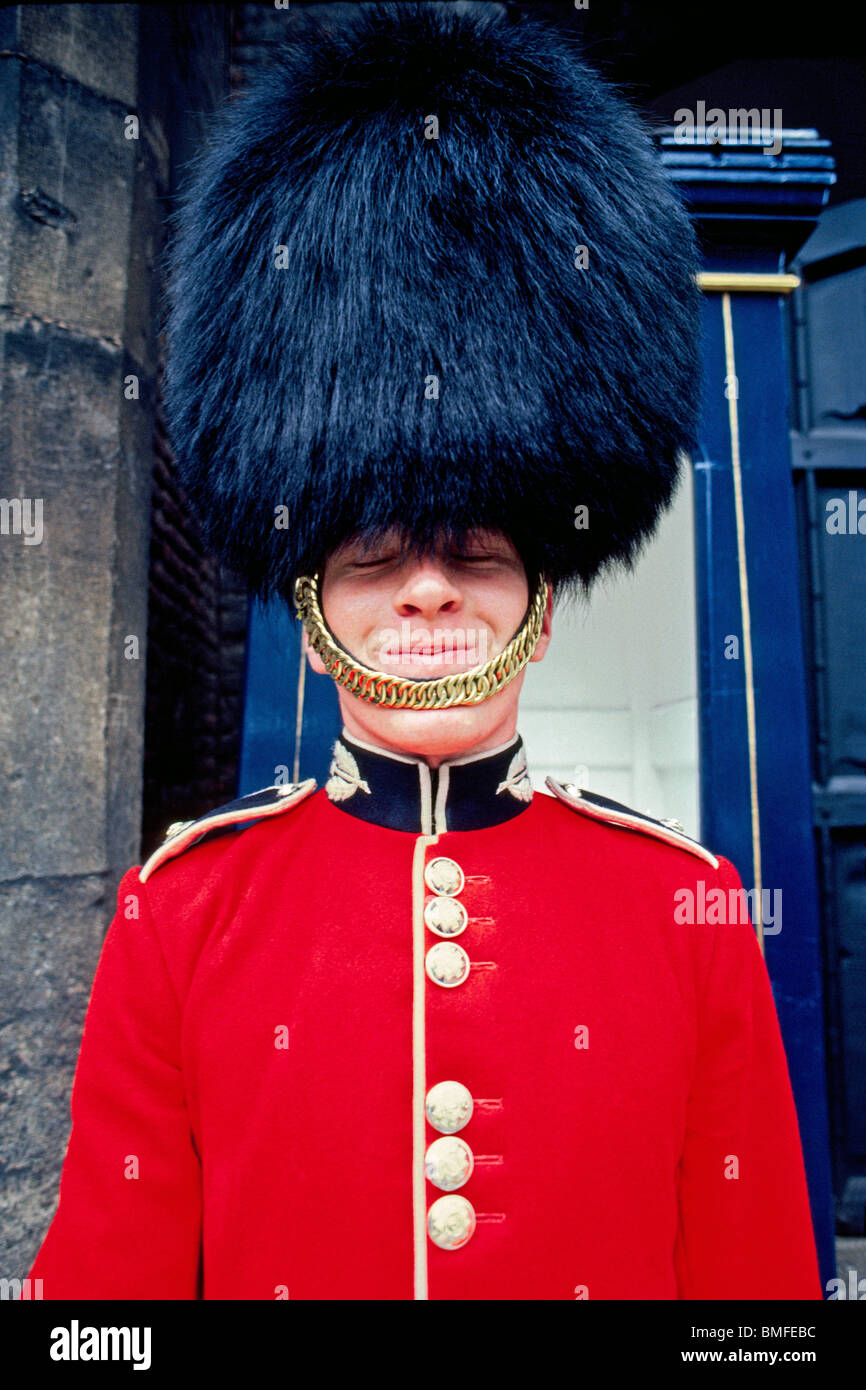 A bashful British palace guard in his traditional red dress tunic and black bearskin hat tries to hide a smile while - Stock Image