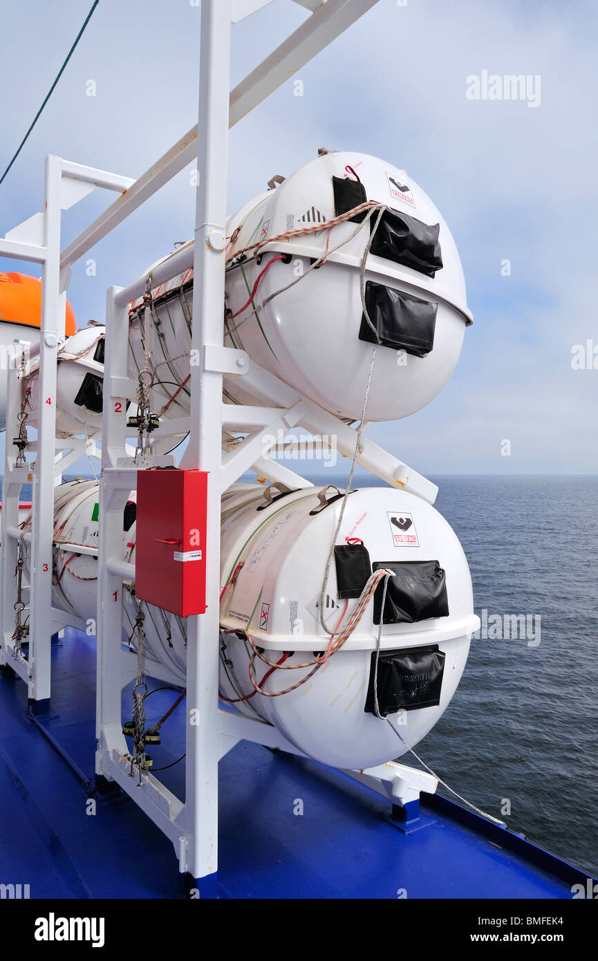 Inflatable liferafts in hard-shelled canisters and lifeboat on board of ferryboat, Europe - Stock Image