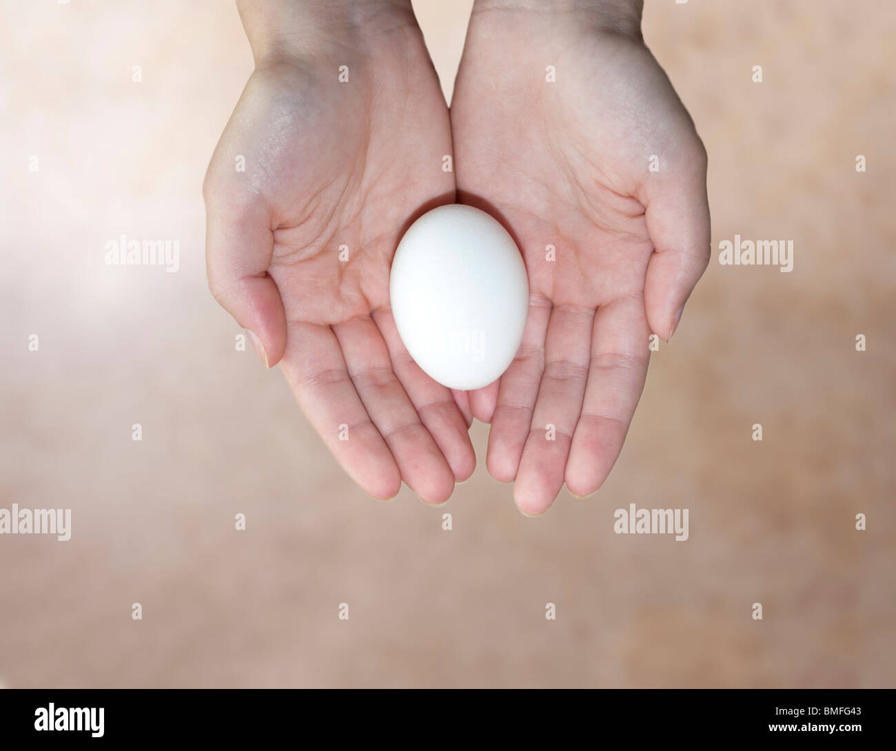 A conceptual image of a young woman's hands holding an egg against a beige background. Concept fertility, concept - Stock Image