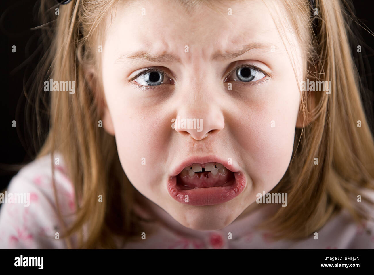 Shot of an Upset Child with Gaps in her Teeth - Stock Image