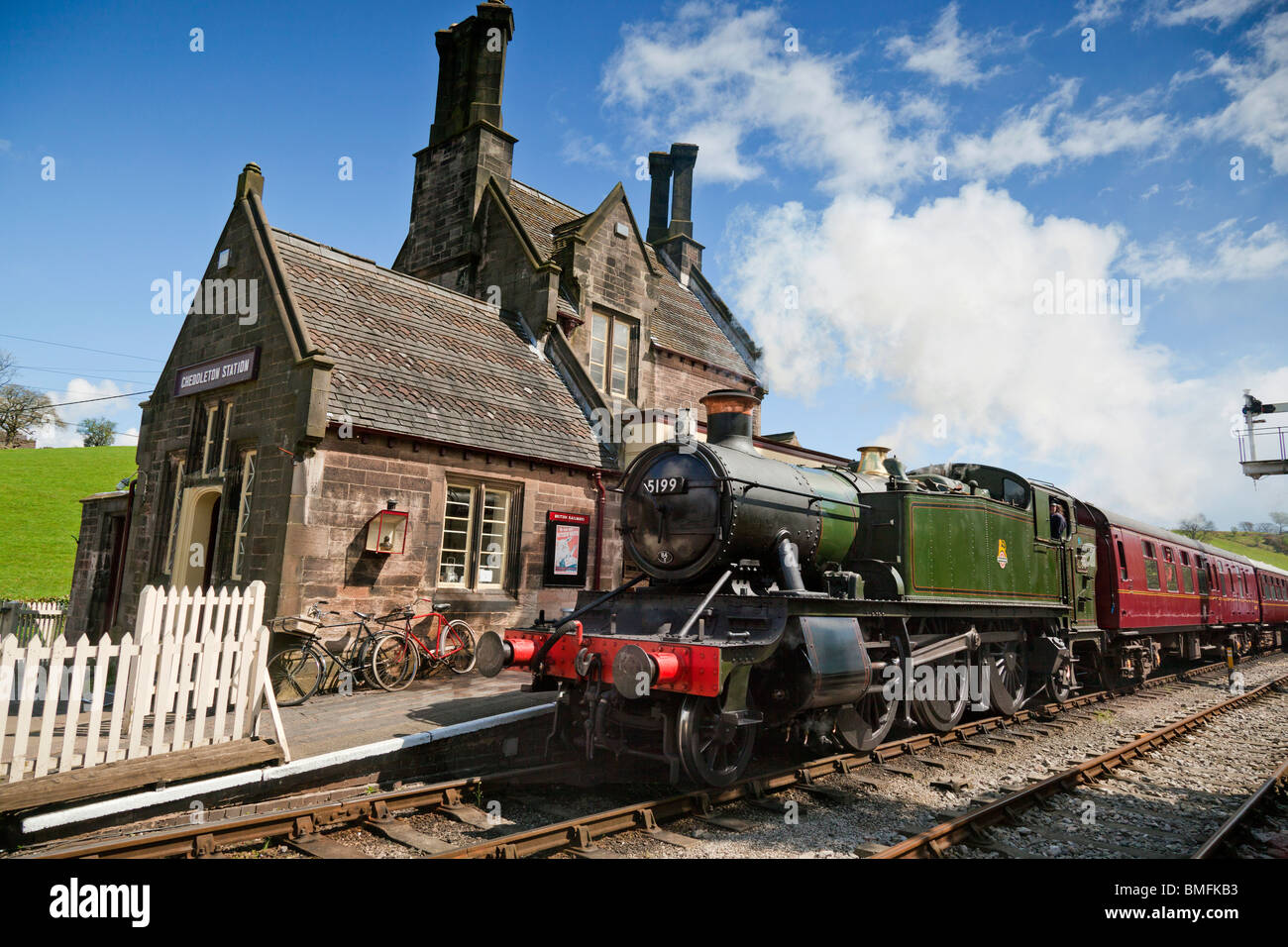 A steam train passes through Cheddleton station on the Churnet Valley Railway. - Stock Image