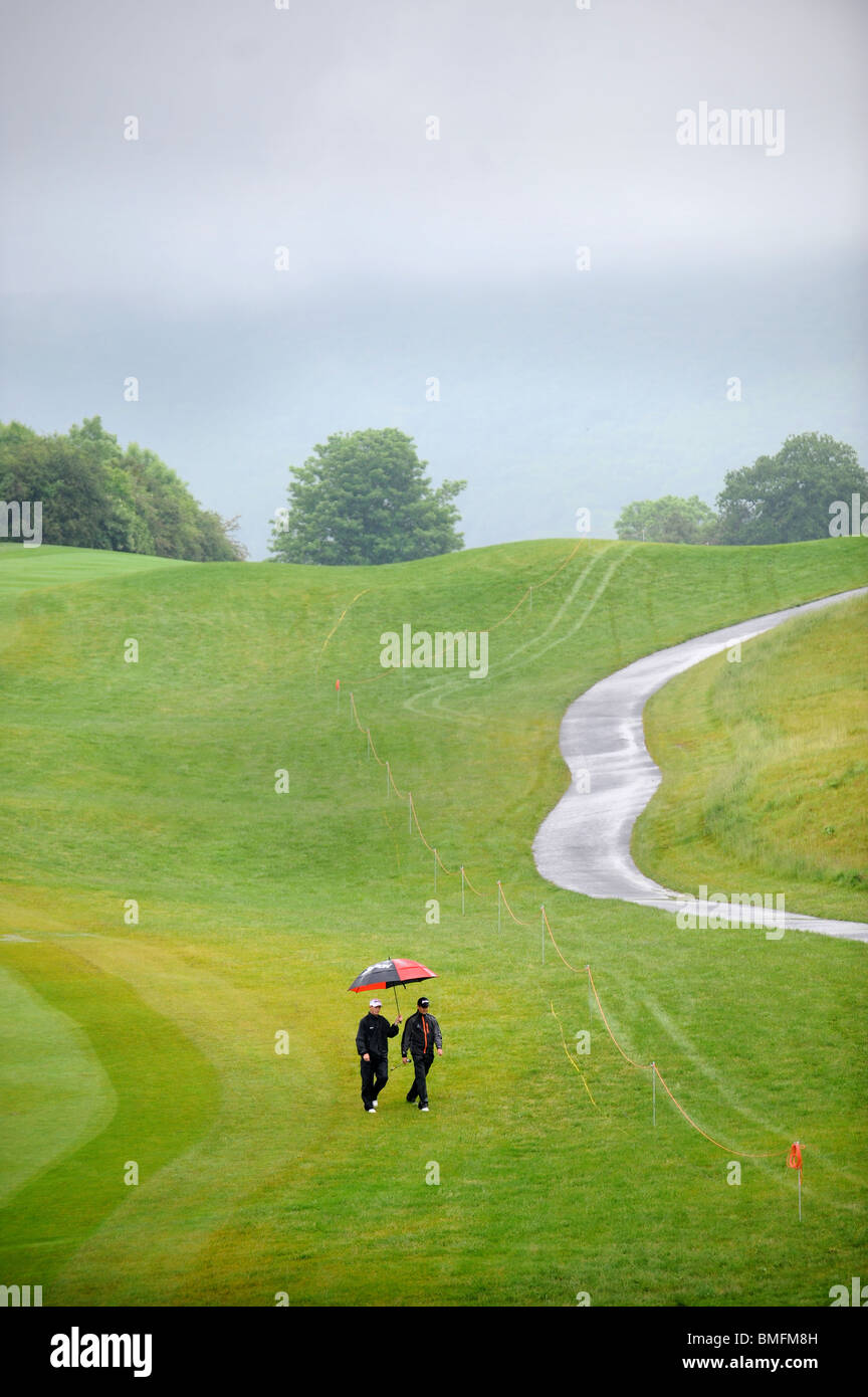 A golfer and his coach walk the course in the rain at the Celtic Manor Wales Open 2008 - Stock Image