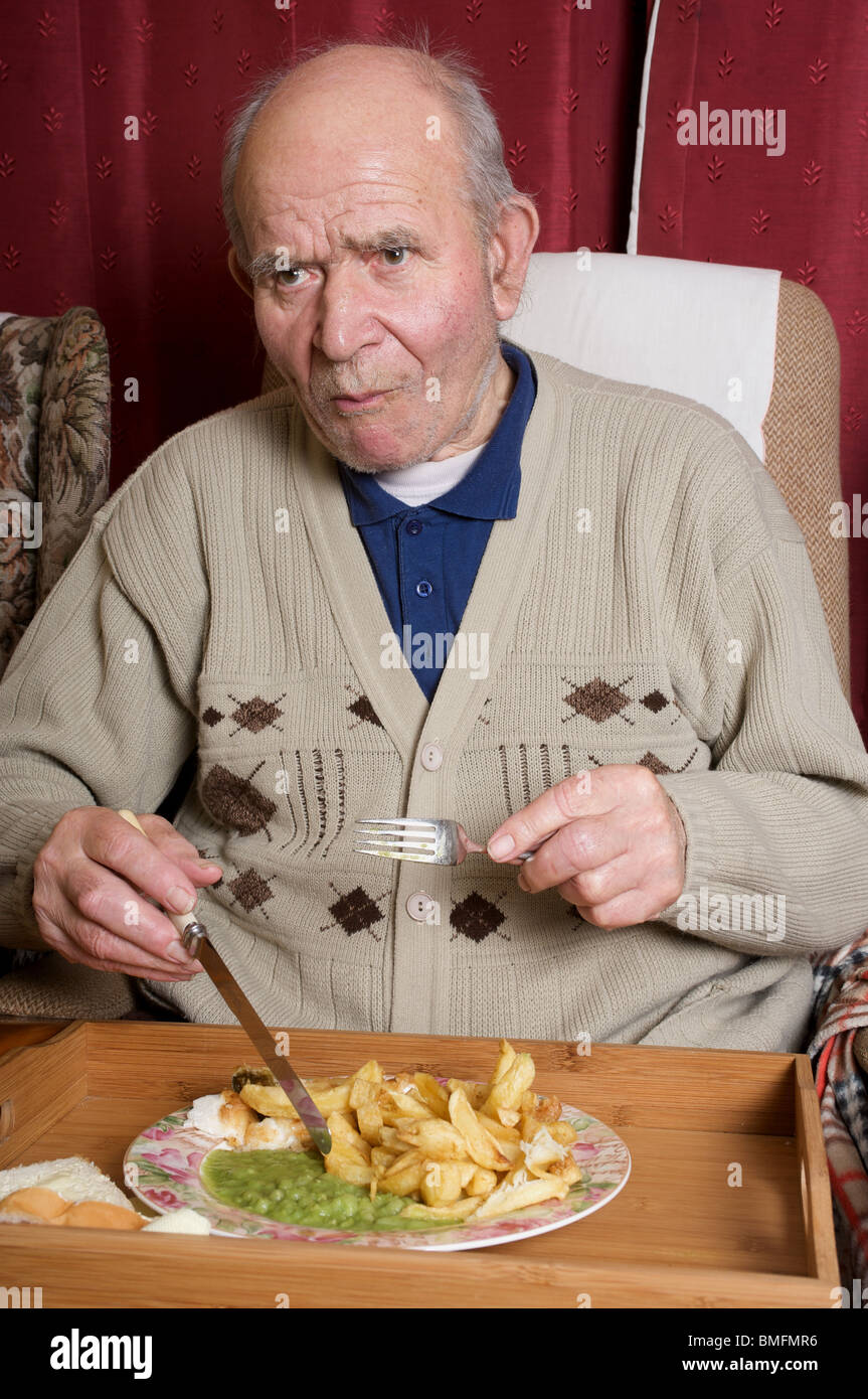 Elderly man eating fish and chips while watching TV. - Stock Image