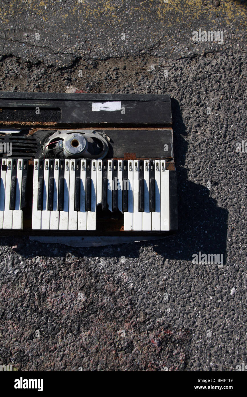 old music synthesizer piano damaged in street - Stock Image