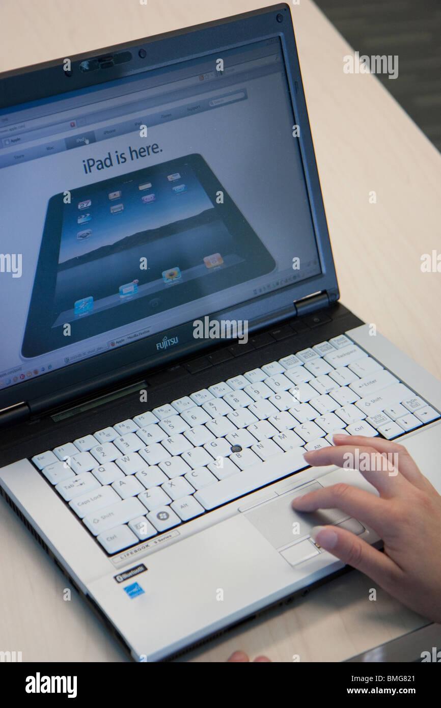 female hand laptop touchpad closeup ipad website - Stock Image
