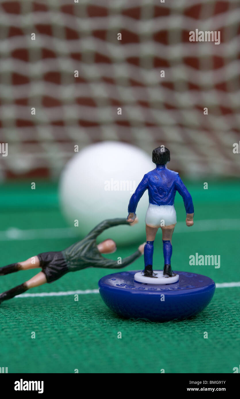 goalkeeper diving to foul player in the box football soccer scene reinacted with subbuteo table top football players - Stock Image