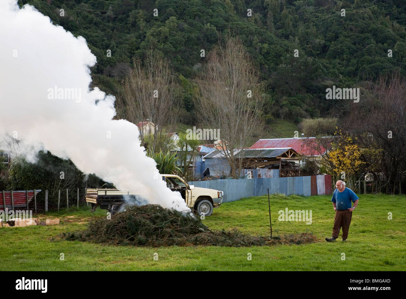 An old man burning leaves and producing a white cloud of smoke in a farm, New Zealand Stock Photo