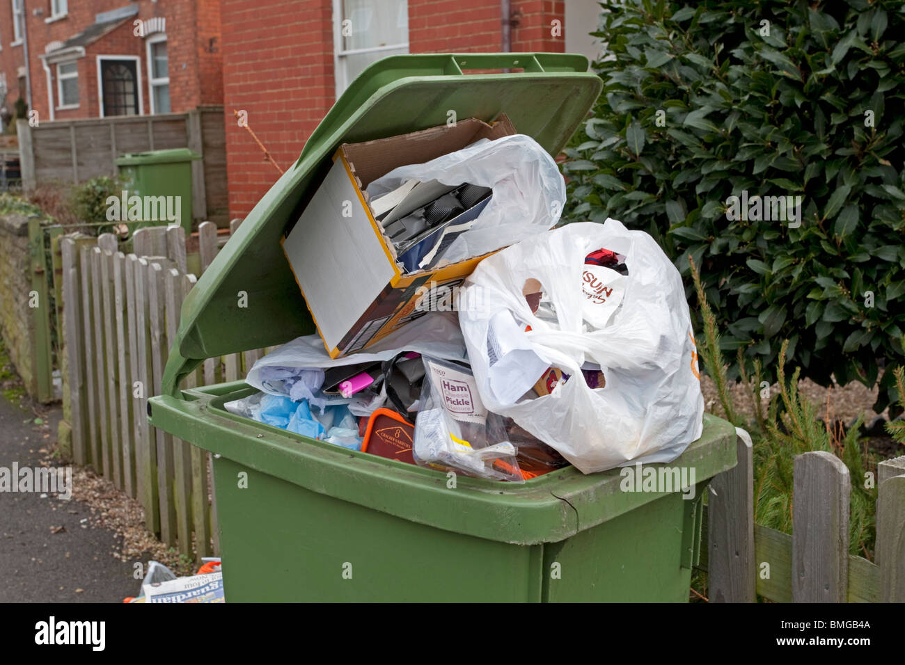 Green domestic household waste bin over full with rubbish some of Stock  Photo - Alamy