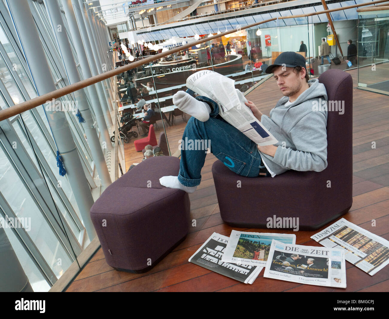 A student reads a newspaper on the Stockholm-Arlanda airport. - Stock Image