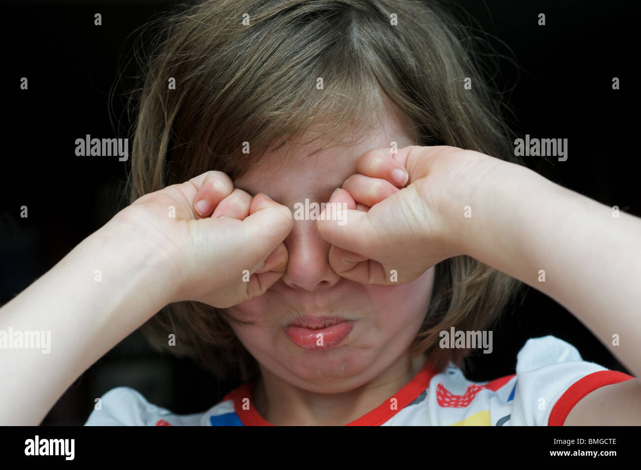 Young girl rubbing her eyes after sobbing - Stock Image