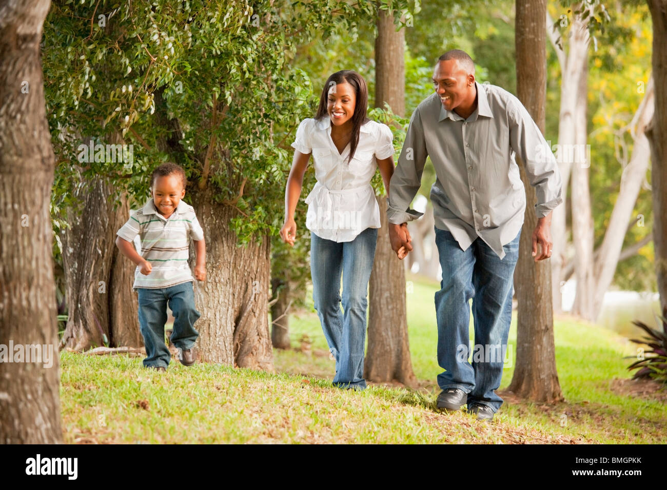 Fort Lauderdale, Florida, United States Of America; A Father And Mother With Their Young Son Walking Through A Park Stock Photo
