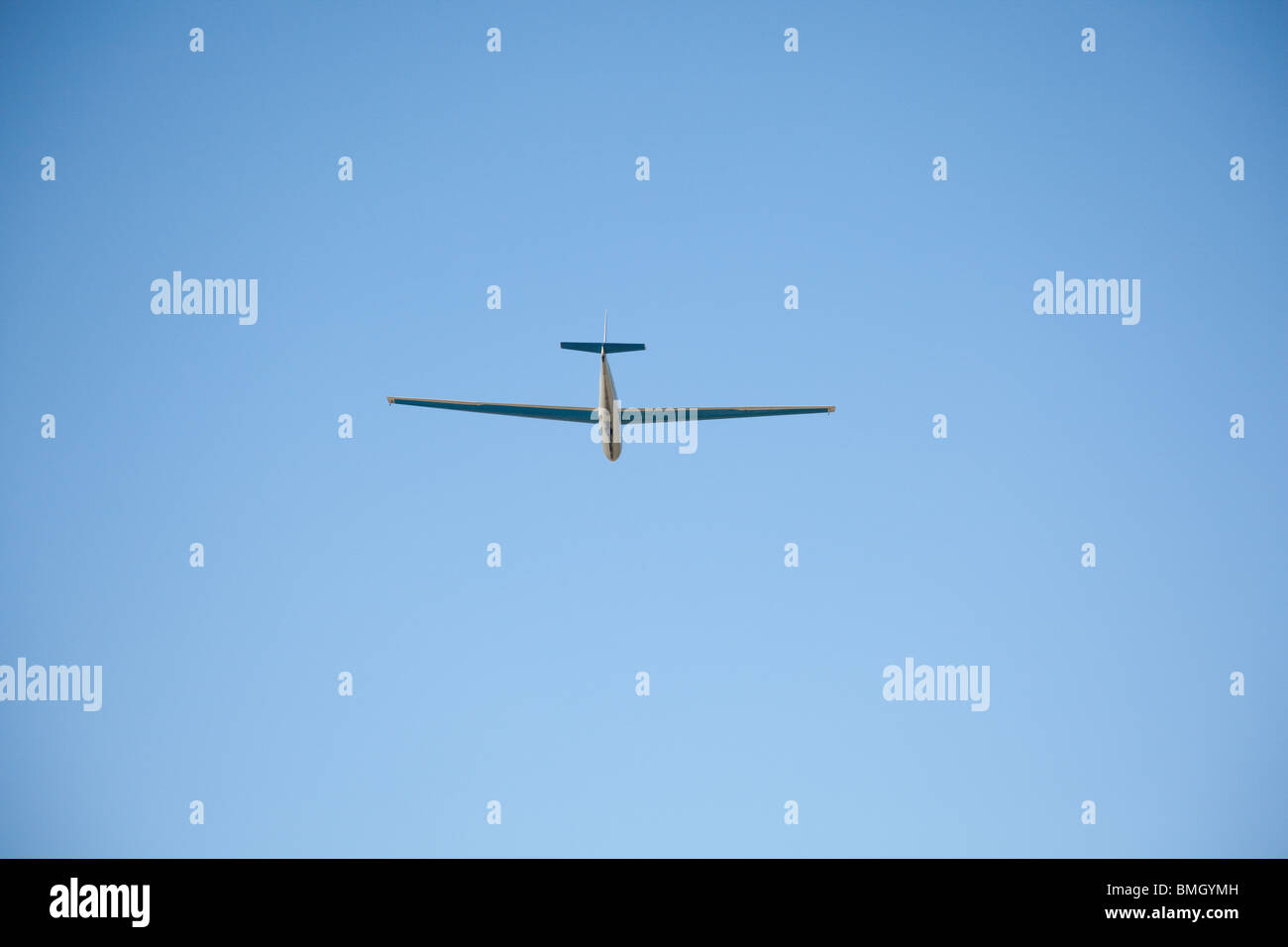 Glider plane against clear blue sky - Stock Image