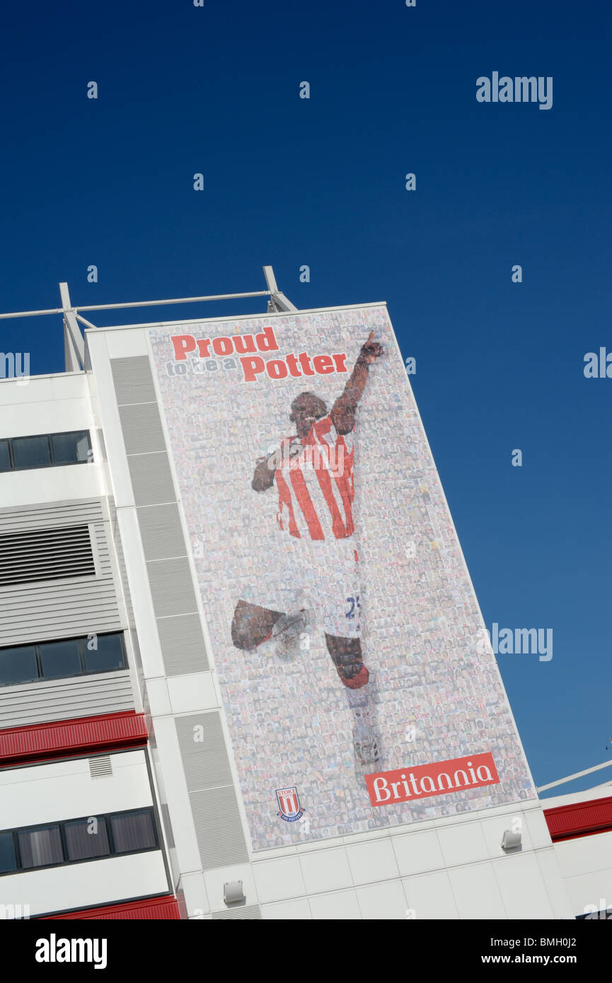 Massive banner covering the side of the Britannia Stadium home of Stoke City FC featuring Stoke player with words - Stock Image