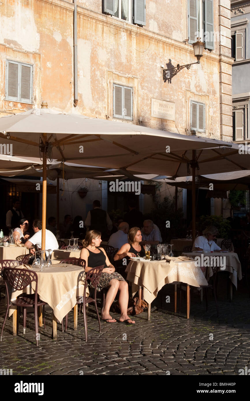 Person sit in a traditional bar in Santa Maria in Trastevere square Rome Italy - Stock Image