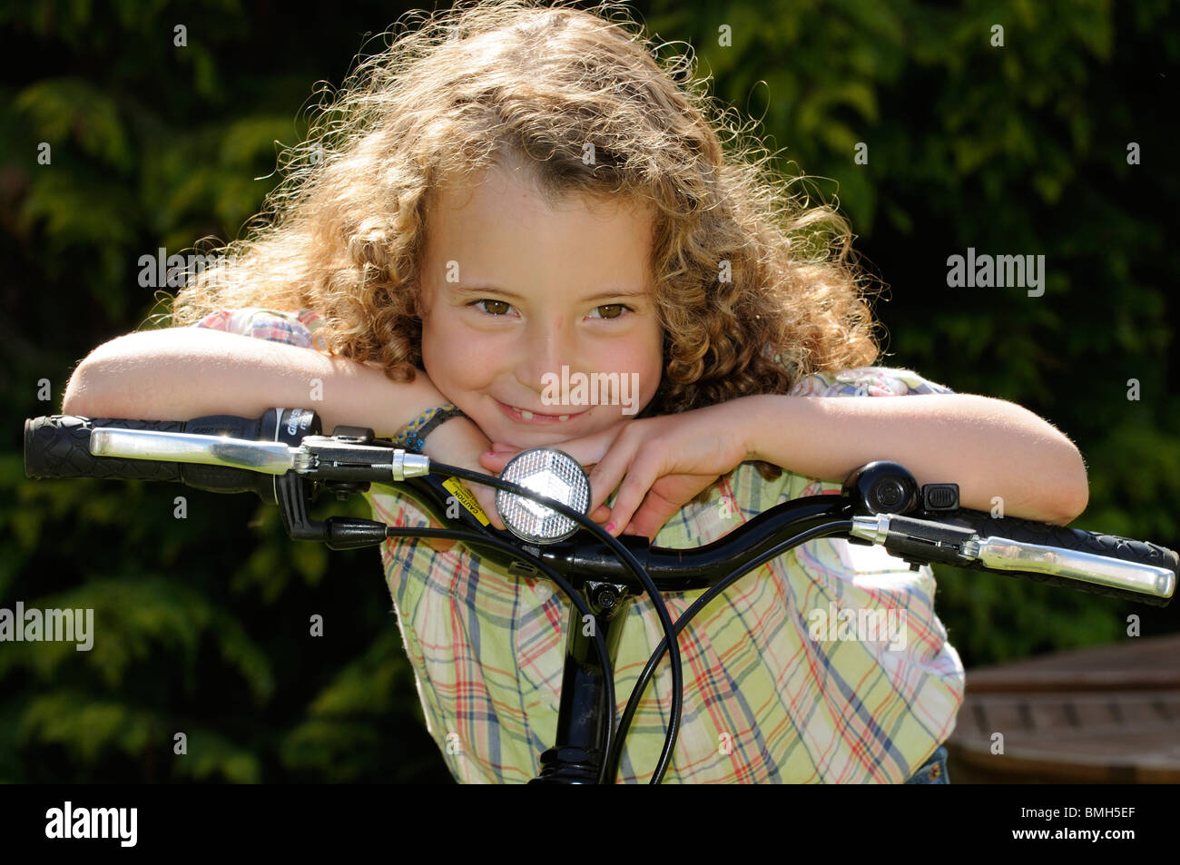 Portrait of a little girl leaning on the handlebars of her bicycle She has her front teeth missing - Stock Image