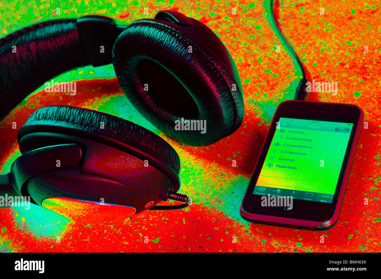 iphone plugged into a pair of headphones - Stock Image