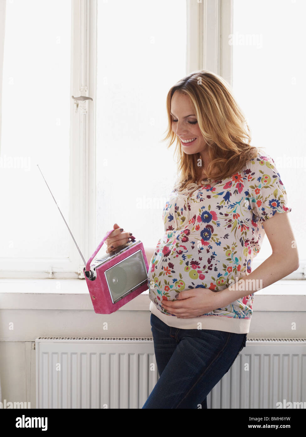 Pregnant woman holding radio to belly Stock Photo