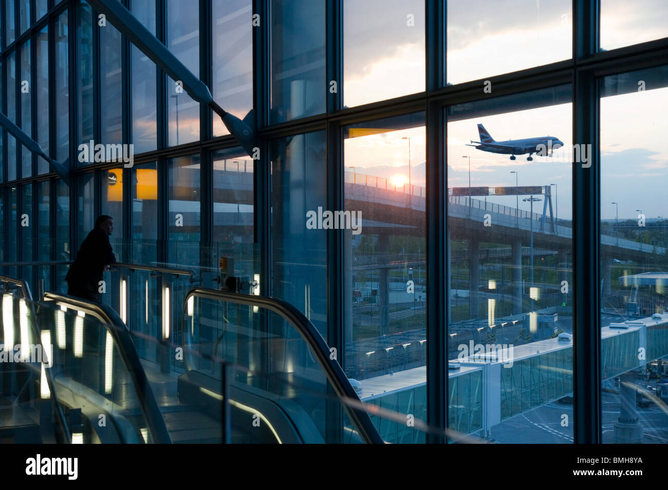 London Heathrow Airport Terminal 5 - departure gate at sunset - BA crew member watches an evening BA departure - Stock Image
