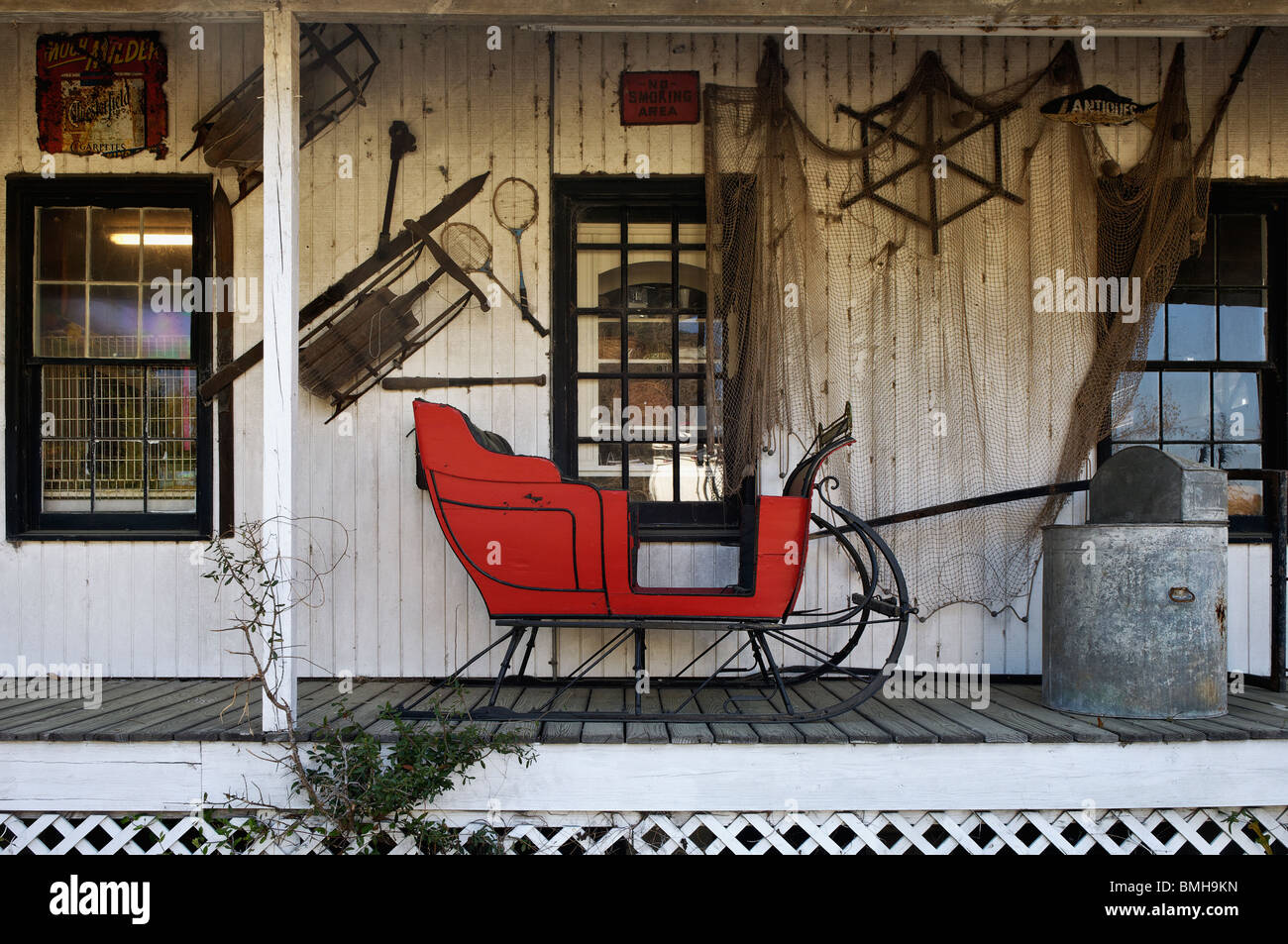 Red Sleigh on the Front Porch at the Thieves Market Antique Store in Mount Pleasant, South Carolina - Stock Image