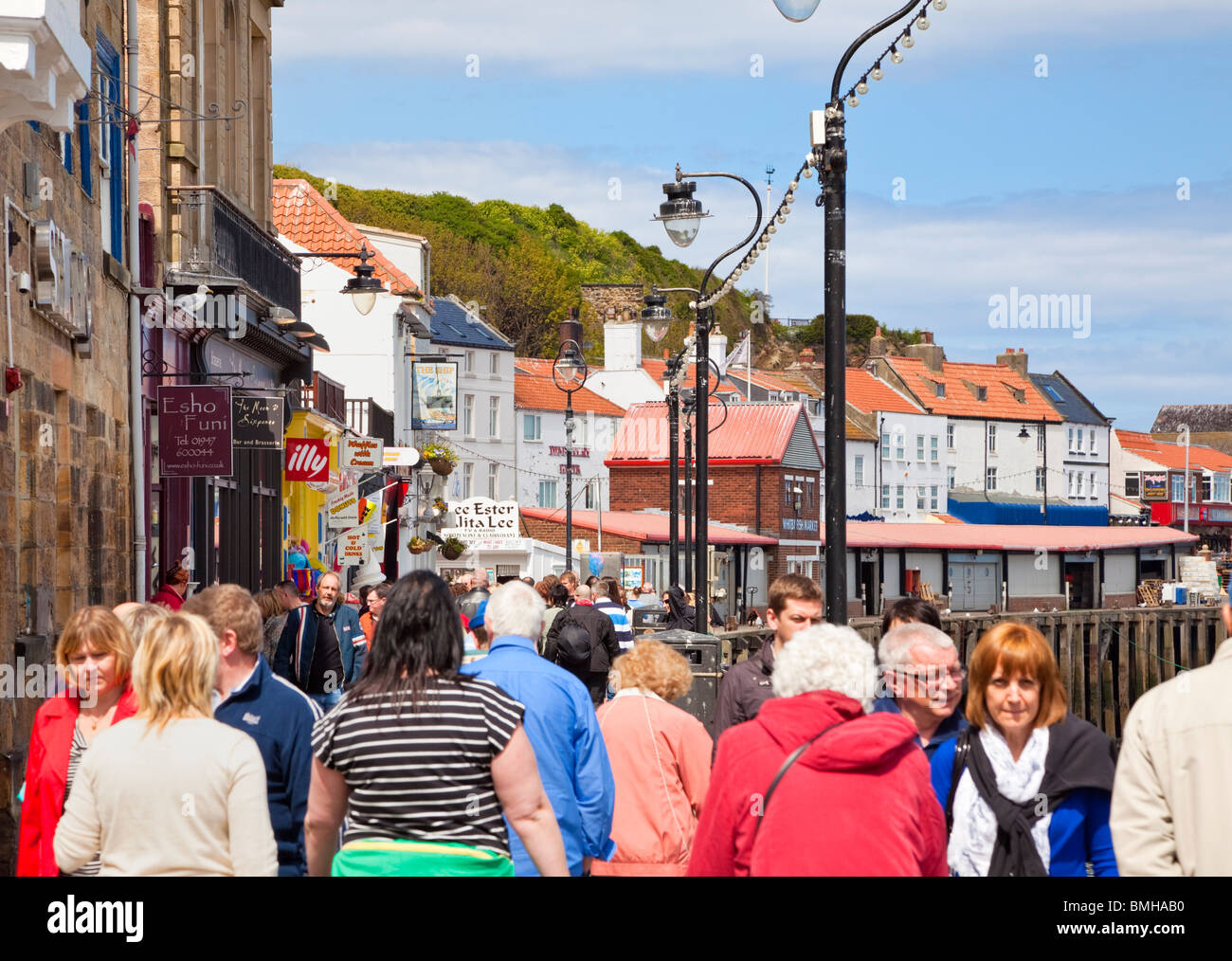 Tourists crowd of people walking beside Whitby Harbour North Yorkshire England UK - Stock Image