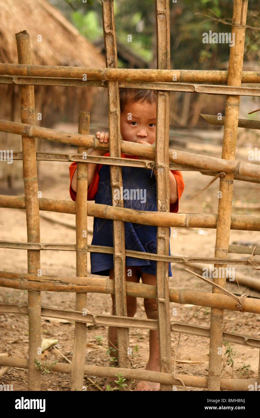 87bc8ea297a Hmong Child looking through a fence in a small village between Pakbeng and  Luang Prabang