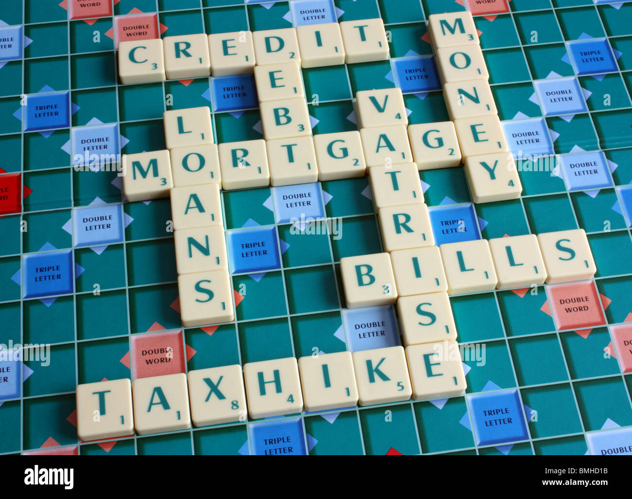 A scrabble board with numerous words implementing debt,credit & money worries - Stock Image