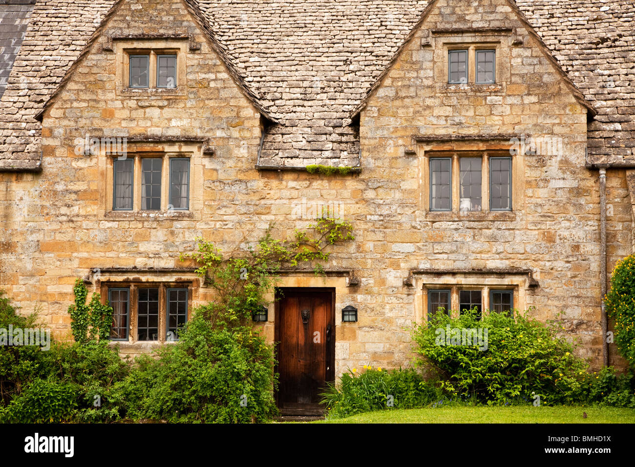 A typical Cotswold stone country house with leaded lights, mullion windows, gable fronted dormer windows and a wooden - Stock Image