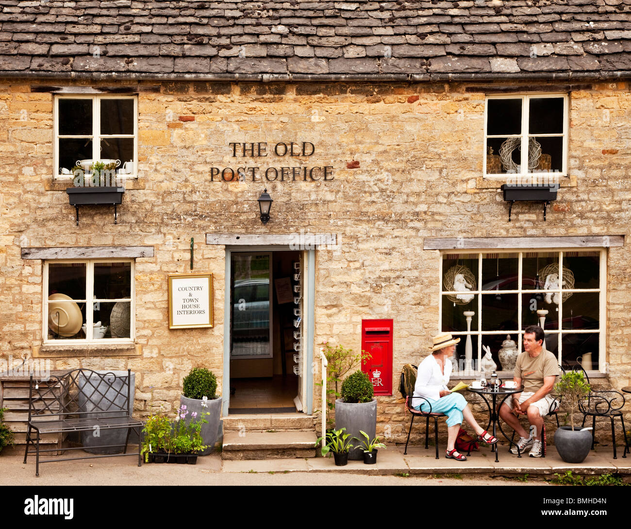 A couple having tea outside the Old Post Office in the Gloucestershire Cotswold village of Guiting Power, England, - Stock Image