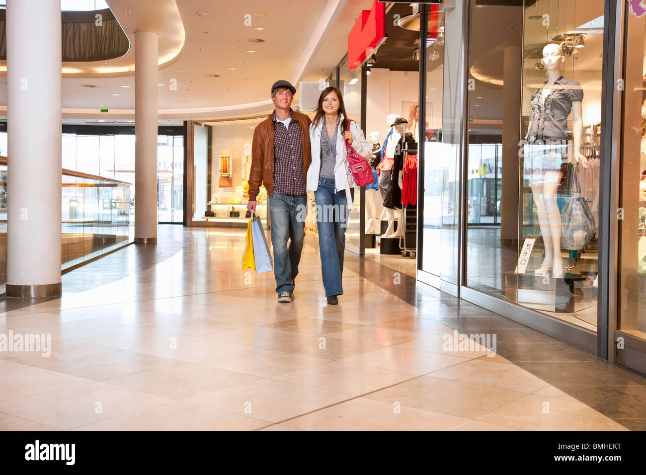 Young couple walking in shopping mall - Stock Image