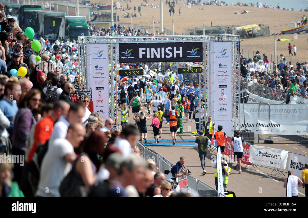 Runners cross the finish line after taking part in first Brighton Marathon 2010 - Stock Image